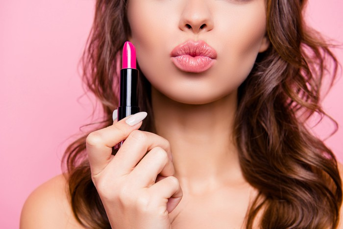A woman pursing her lips and holding up pink lipstick.