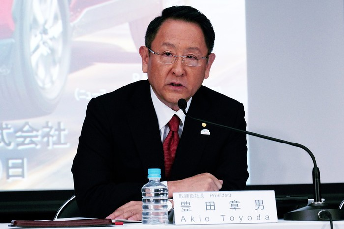 Akio Toyoda is shown seated at a table during a press conference.