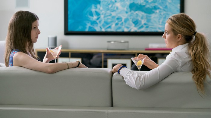 Stephanie (actress Anna Kendrick, left) and Emily (actress Blake Lively) in a scene from A Simple Favor. They are sitting on a couch, facing each other, drinking cocktails.