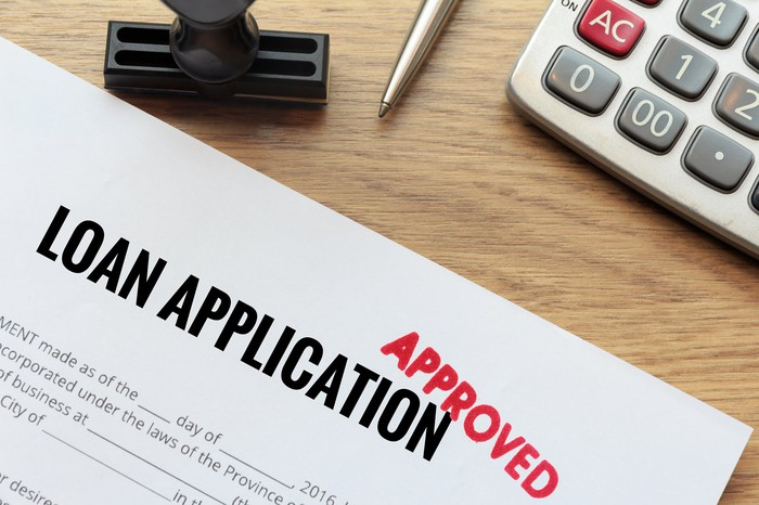 Loan application with approved stamped in red.