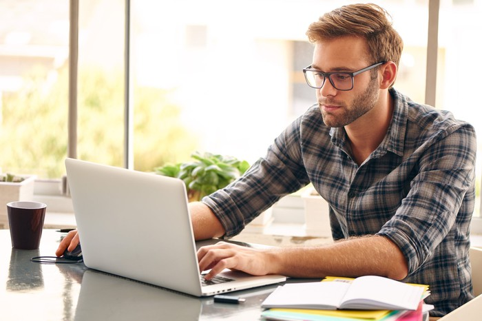 Man with glasses and a flannel shirt working on a notebook computer