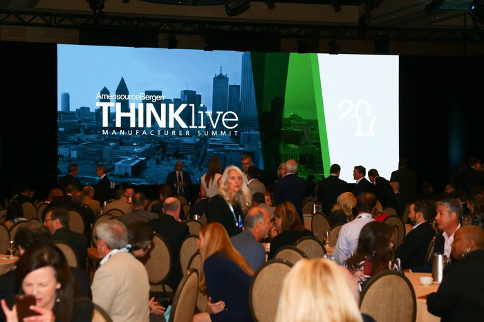 Group of people attending a conference, with a screen showing a graphic for AmerisourceBergen's Thinklive manufacturer summit.