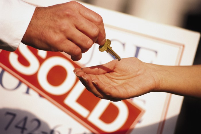 Man handing home keys to a buyer with a sign in the background that says sold.