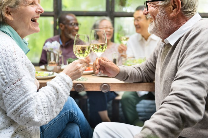 Mature man and woman celebrating toasting glasses of wine