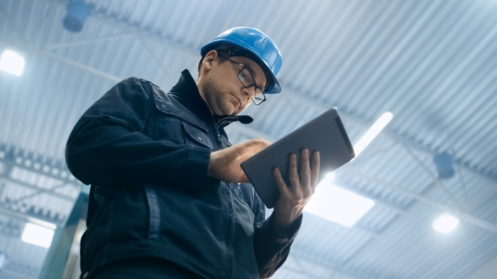 A man in a hard hat works on a tablet.