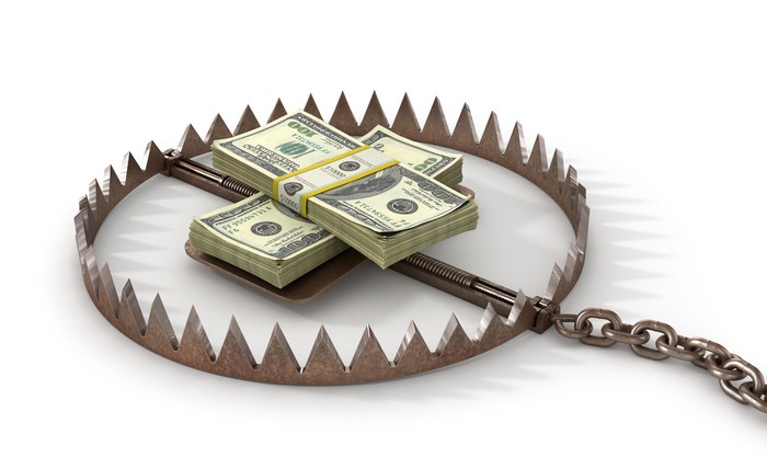 Two neat piles of hundred-dollar bills lying in the center of a bear trap.