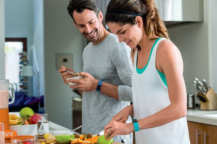 A couple wearing Fitbit Charge bracelets in a kitchen.
