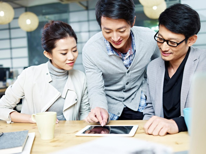 Three young professionals look at a tablet.