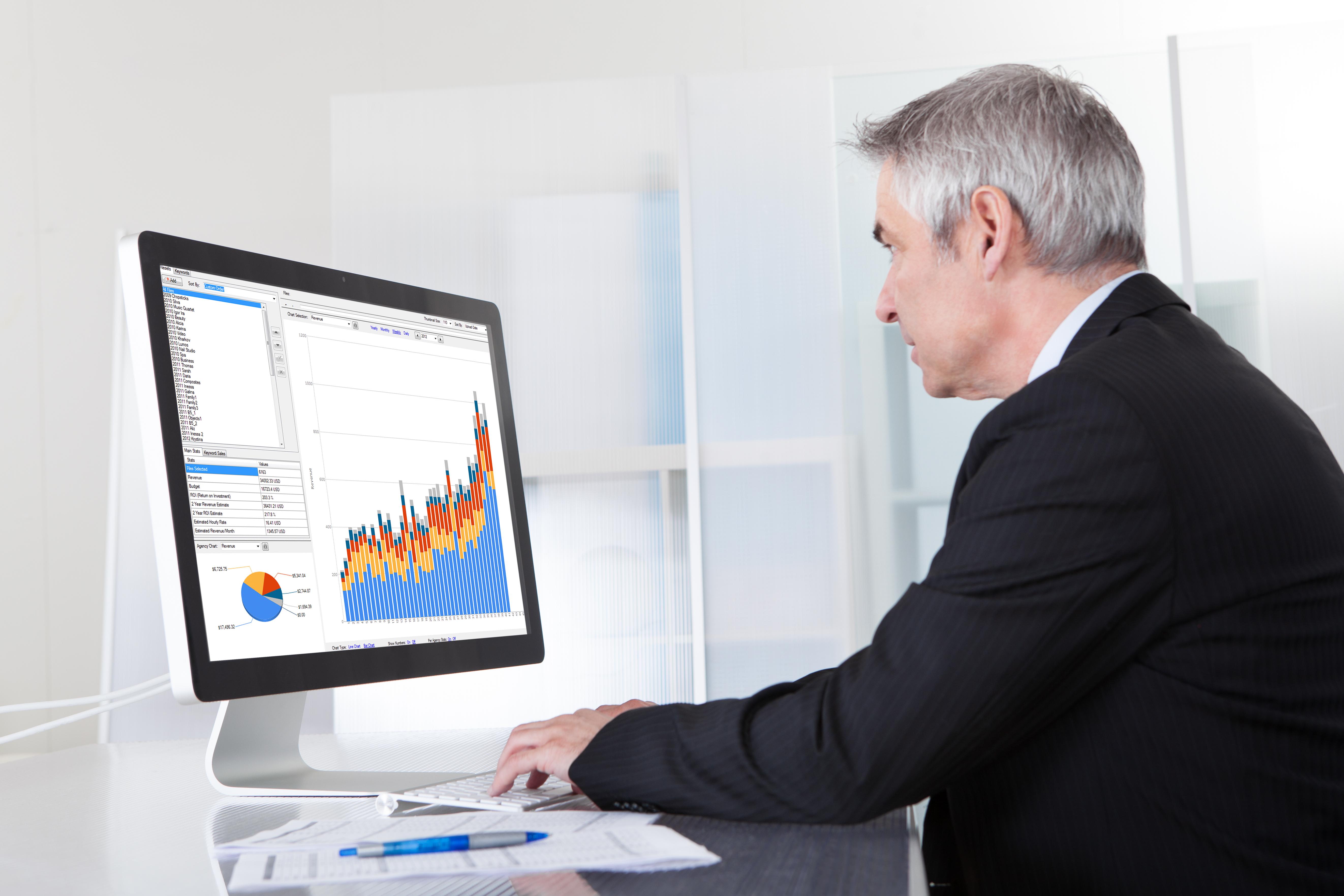 Senior man looking at computer screen with graphs and charts.
