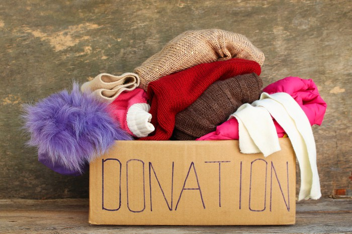 A cardboard box labeled donation, overflowing with clothes