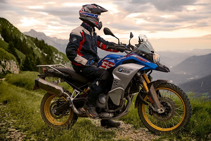 A BMW F 850 GS Adventure, a motorcycle designed for rugged terrain, is shown with a rider in a mountain setting.