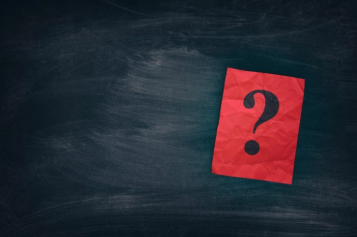 A question mark on a red card sitting against a chalkboard.