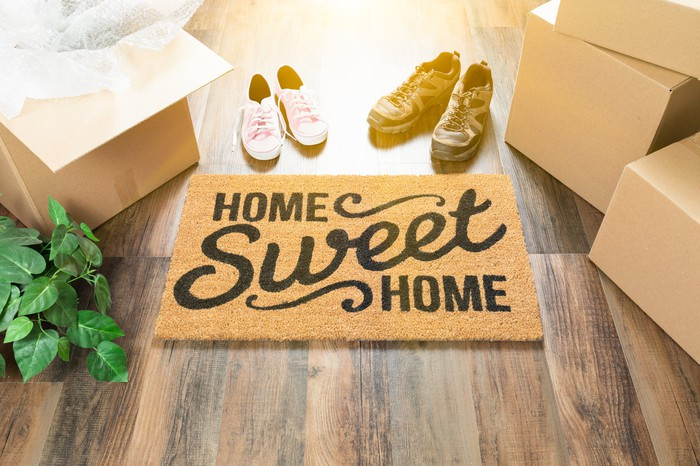 Home Sweet Home Welcome Mat, Moving Boxes, Shoes and a Plant on Hard Wood Floors.