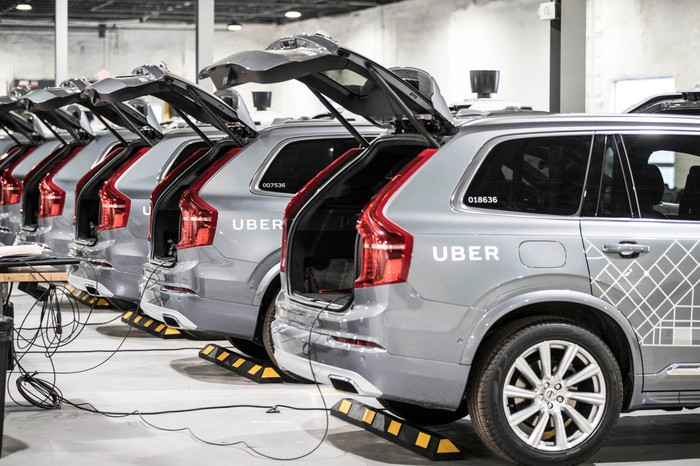 A line of Uber's autonomous SUVs with their trunks open.