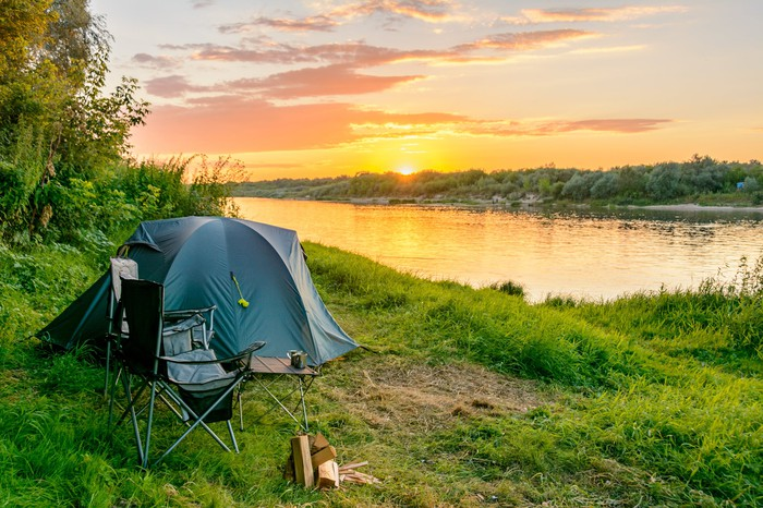 Image of a tent set up with lake in the background.