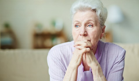 senior woman worried thinkng with hands clasped in front of face
