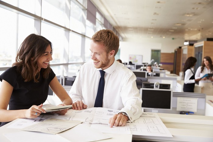 Male and female worker in office together smiling and looking at papers