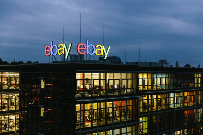 Office building with lights turned on under a dark sky with the eBay logo displayed on the roof of the building.