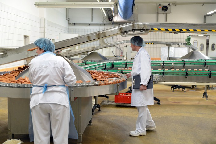 Two employees in hairnets in a food manufacturing facility