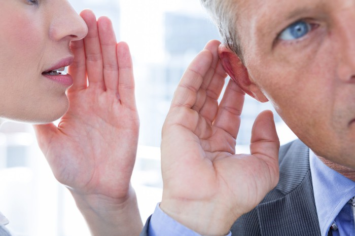Woman with hand held up to her mouth next to a man with his hand held up to his ear