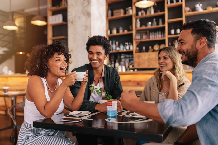 Two men and two women meeting in a coffee shop