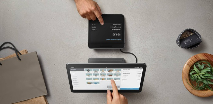 An employee and customer interact with the two displays included with Square Register.