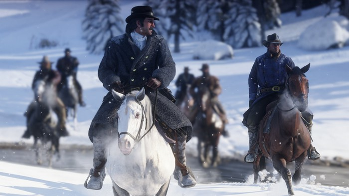 """A screenshot from """"Red Dead Redemption 2"""" showing a number of cowboys on horseback riding across a snowy landscape."""