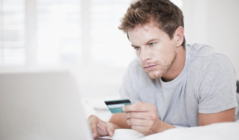 man with credit card shopping on laptop computer