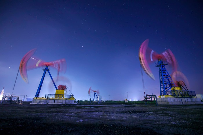 Oil pumps in motion at night.