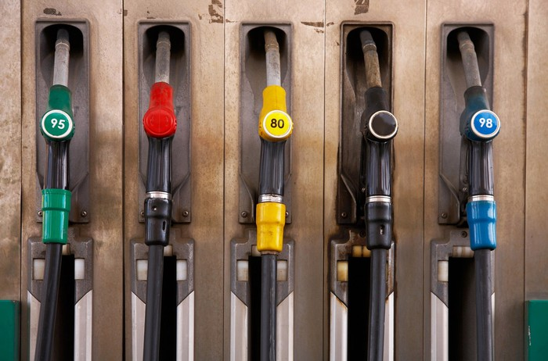 Five fuel pump nozzles in different colors.