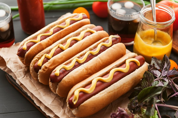 American hot dog with condiments on a dark wooden background.