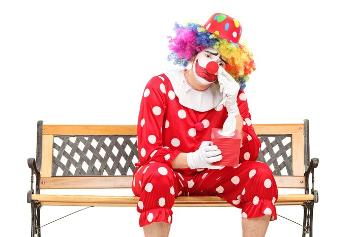 Sad clown sitting on a bench.