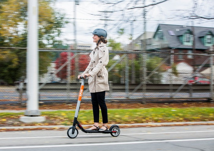 A woman riding a Spin e-scooter in a bicycle lane on a street in Detroit.