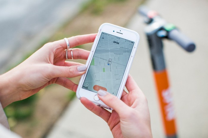 A close-up of a woman's hands with an iPhone running the Spins app. A Spin scooter is visible in the background.