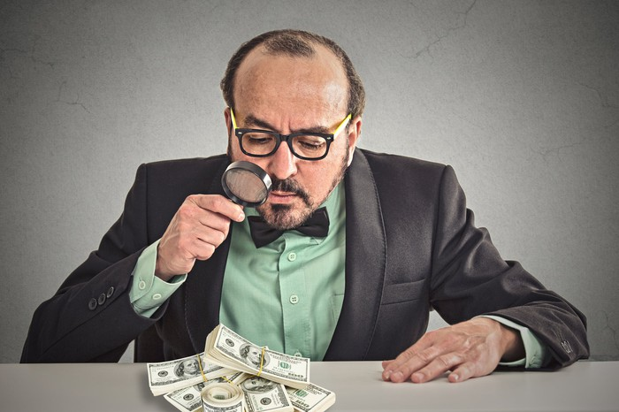 A businessman in a suit looking at a pile of money with a magnifying glass