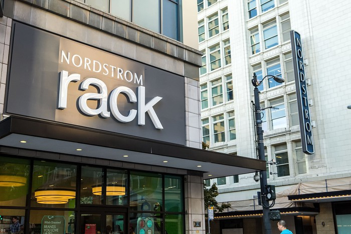The exterior of a Nordstrom Rack store, with the Nordstrom Seattle flagship store in the background