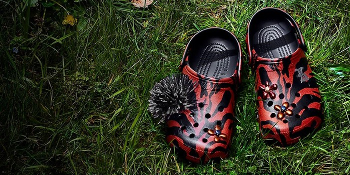Two red and black Crocs shoes on a grass lawn.