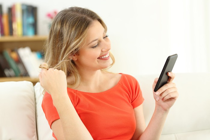 A woman twirls her hair while looking at her smartphone.