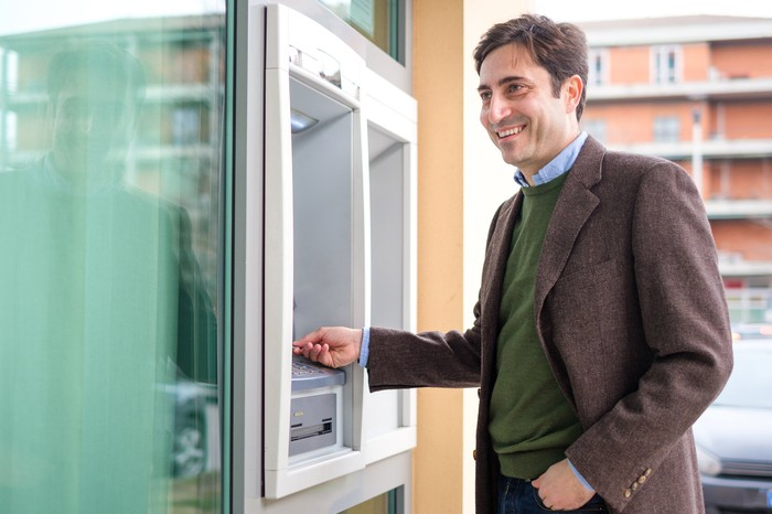 Smiling man using an ATM in a banking center in Italy.