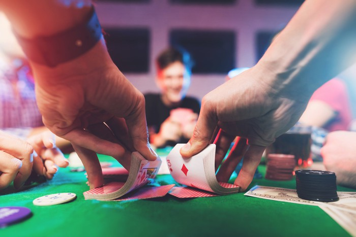A man's hands shuffle a deck of cards on a green felt-covered table