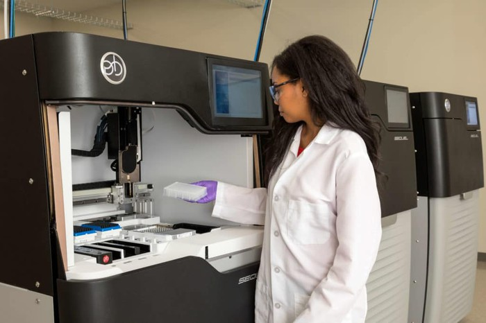 Woman in lab coat using PacBio's Sequel system.