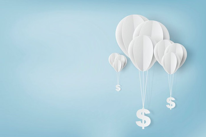 Balloons hoisting dollar signs into the air.