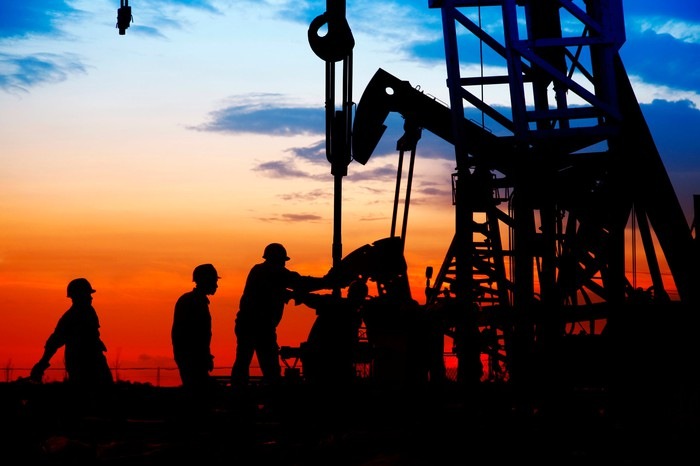 Men in hard hats stand near an onshore oil rig silhouetted at sunset.