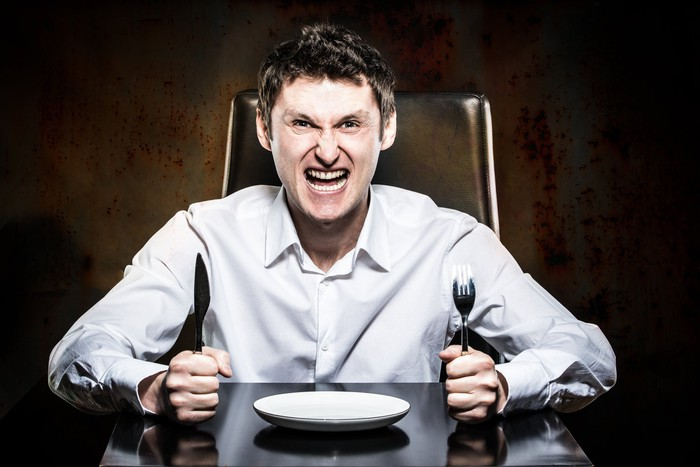 Angry man holds knife and fork in front of empty plate