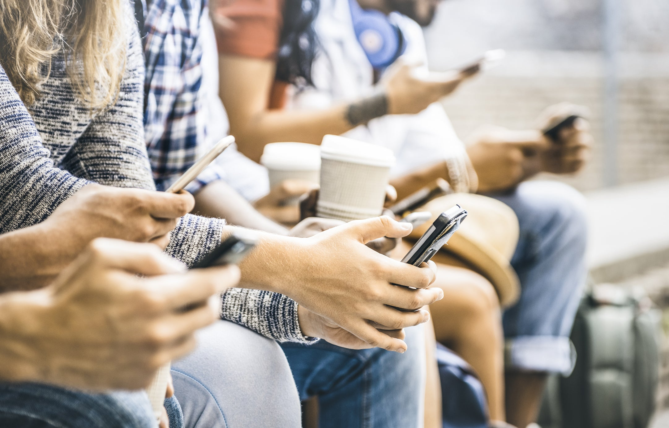 People sitting next to each other with smartphones in their hands