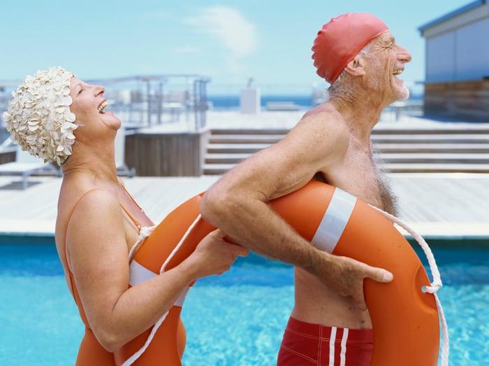 Seniors laugh while walking beside a swimming pool.