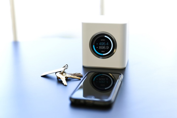 Contemporary design in Ubiqiuiti Networks router next to a smartphone and keys.