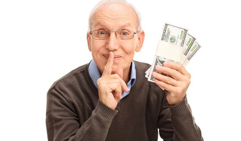 retired man holding wads of cash