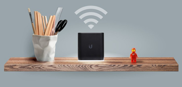 Black Ubiquiti Networks router on a wooden shelf.