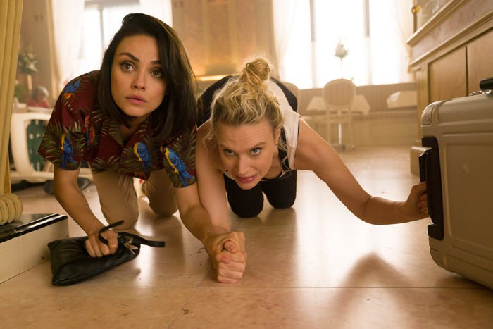 Two women crawling across the floor with concerned looks on their faces.